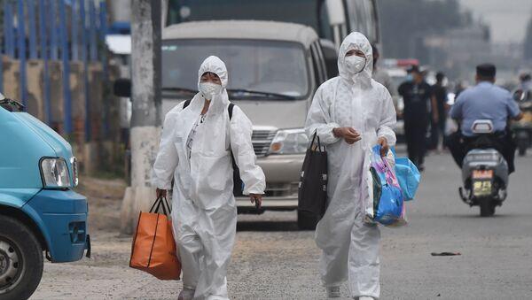 Mieszkańcy w odzieży ochronnej i maskach na targu Xinfadi - Sputnik Polska