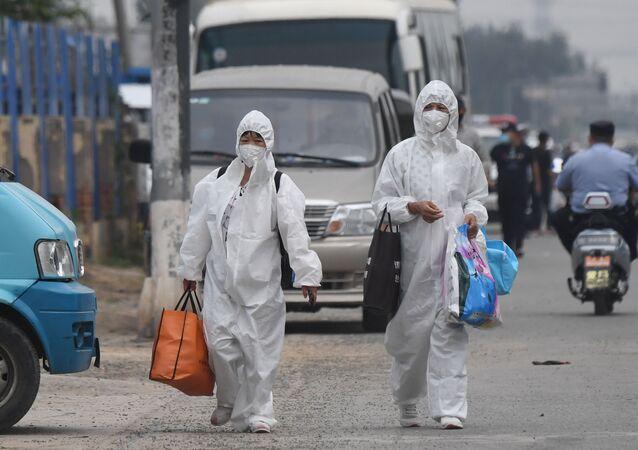 Mieszkańcy w odzieży ochronnej i maskach na targu Xinfadi