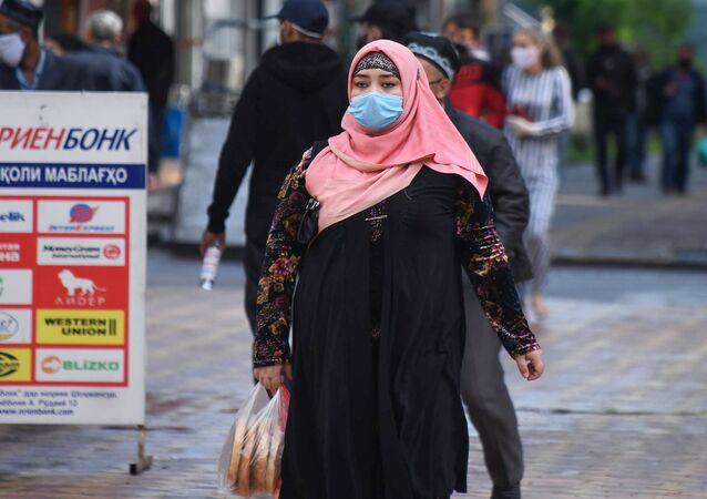 Kobieta w masce ochronnej na jednej z ulic Duszanbe
