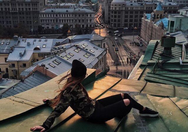 Dziewczyna patrzy na zachód słońca siedząc na dachu w centrum Moskwy