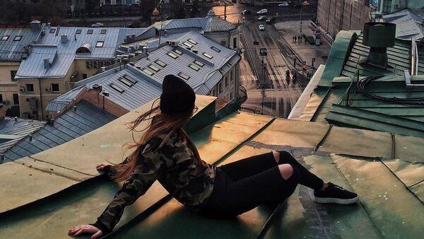 Dziewczyna patrzy na zachód słońca siedząc na dachu w centrum Moskwy - Sputnik Polska