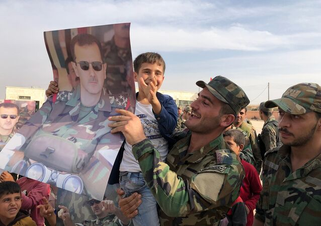 Dzieci i wojskowi z plakatami z portretem prezydenta Syrii Baszara al-Asada w mieście Manbidż w Syrii wyzwolonym przez syryjską armię rządową