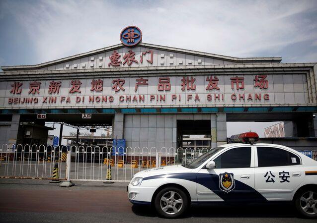 Radiowóz policyjny przy zamkniętym rynku Sinfadi w Pekinie