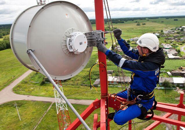 Instalator montuje przekaźnikową antenę radiową na wieży komórkowej