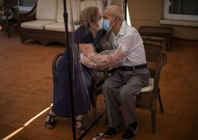 Agustina Canamero i Pascual Perez przytulają się przez ekran z folii w domu opieki w Barcelonie