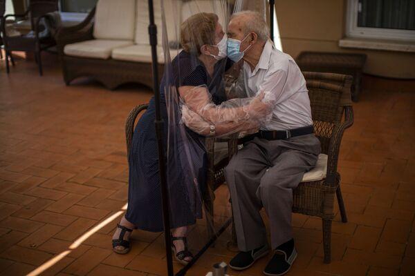 Agustina Canamero i Pascual Perez przytulają się przez ekran z folii w domu opieki w Barcelonie  - Sputnik Polska