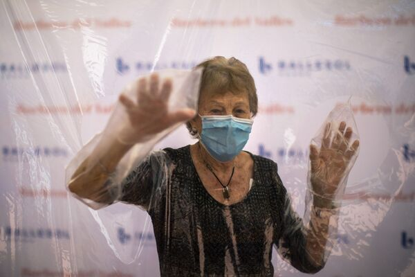 96-letnia Isabelle Perez Lopez w masce medycznej i rękawiczkach ochronnych przed spotkaniem z córką w domu opieki w Barcelonie - Sputnik Polska