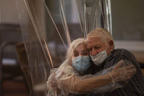 Dolores Reyes Fernandez, 61 lat, po raz pierwszy od 4 miesięcy ściska swojego ojca José Reyesa Lozano w domu opieki w Barcelonie - Sputnik Polska