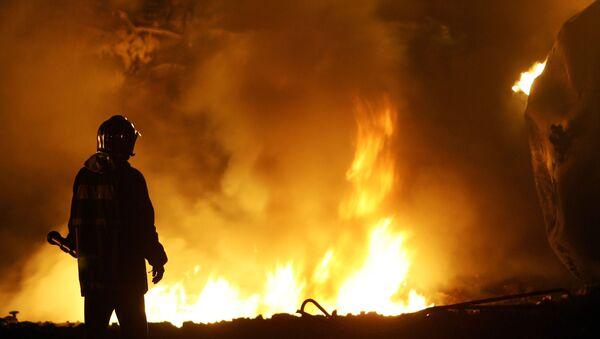 Członek Straży Pożarnej podczas gaszenia pożaru - Sputnik Polska