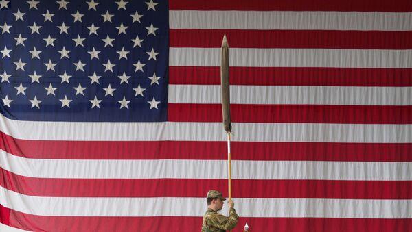 Amerykański żołnierz trzyma flagę podczas ceremonii wojskowej w koszarach Storck w Illesheim w Niemczech - Sputnik Polska