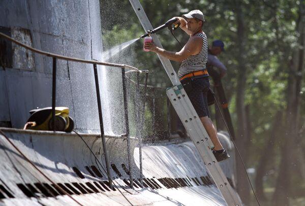 Mężczyzna czyści kadłub łodzi podwodnej M-261 w Krasnodarze - Sputnik Polska