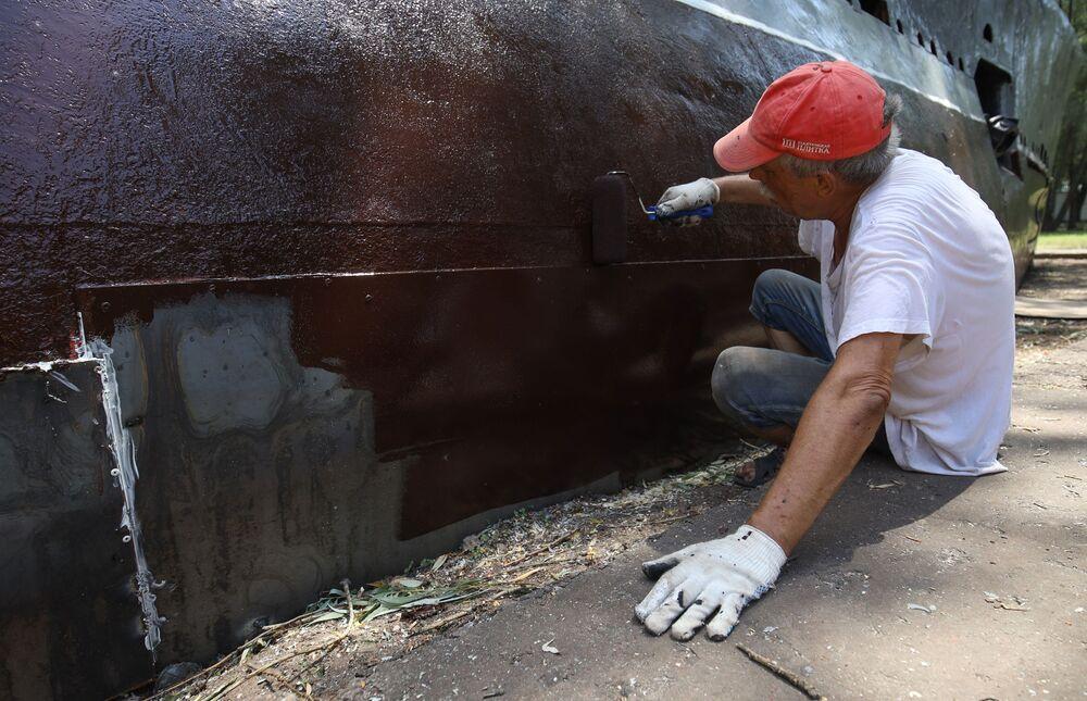 Mężczyzna czyści kadłub łodzi podwodnej M-261 w Krasnodarze