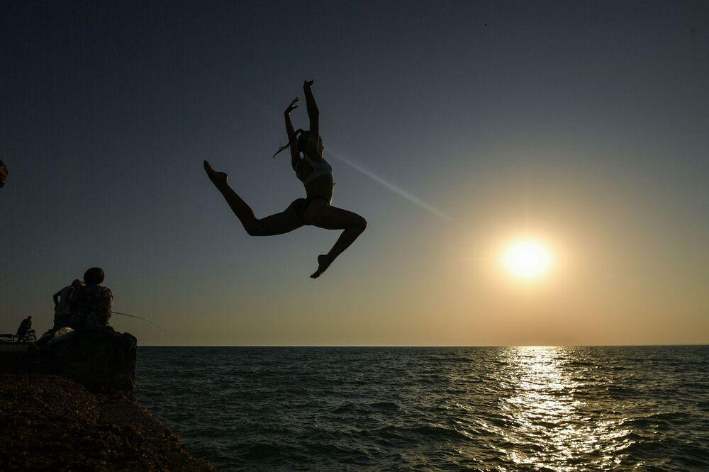 Dziewczyna podczas skoku z molo na plaży w miejskiej osadzie Novofedorivka