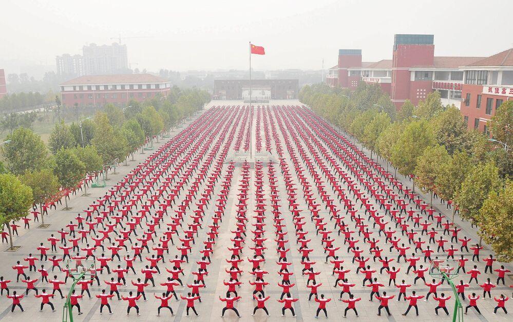 Studenci uprawiają Qigong na szkolnym dziedzińcu