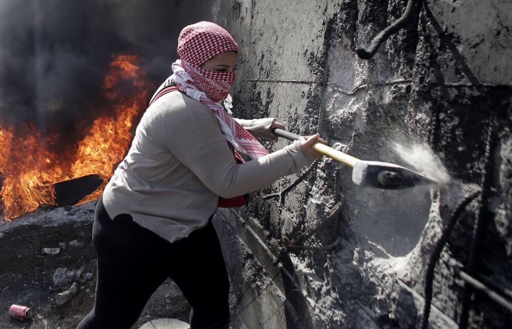 Palestyńska kobieta burzy ścianę między miastem Abu Dis na Zachodnim Brzegu i zachodnią Jerozolimą