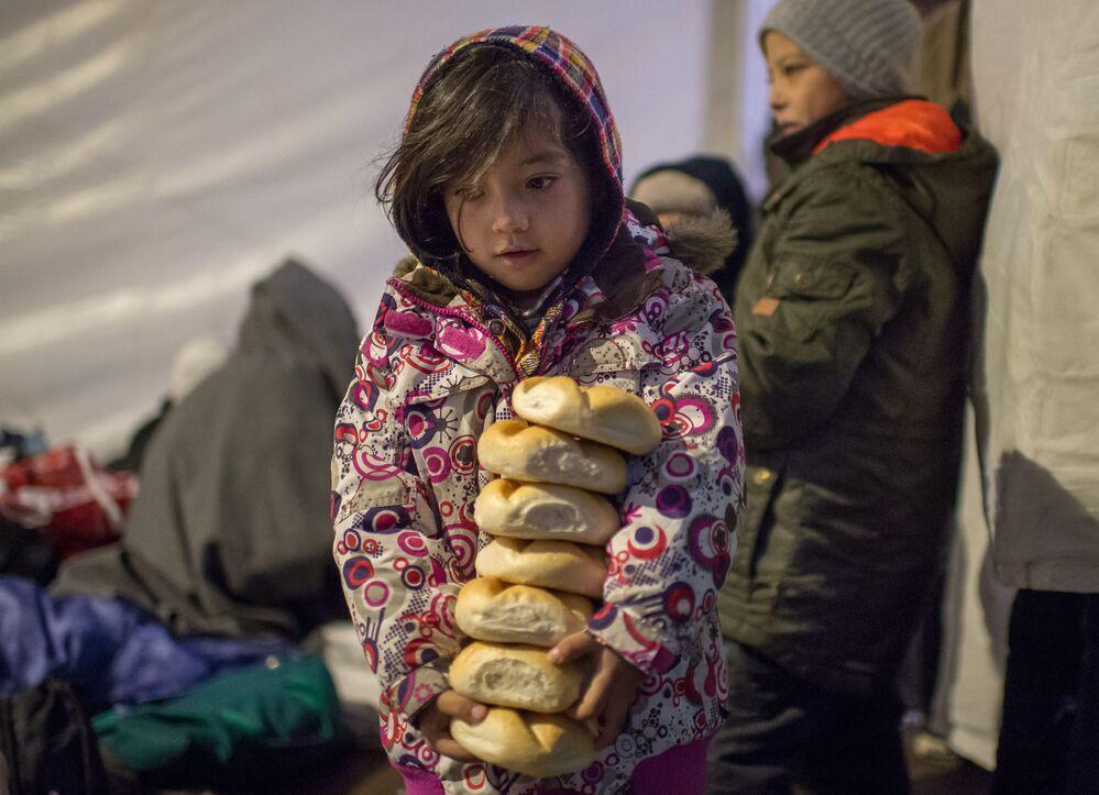 Mała dziewczyna przyniosła bułeczki do namiotu w obozie uchodźców w Austrii