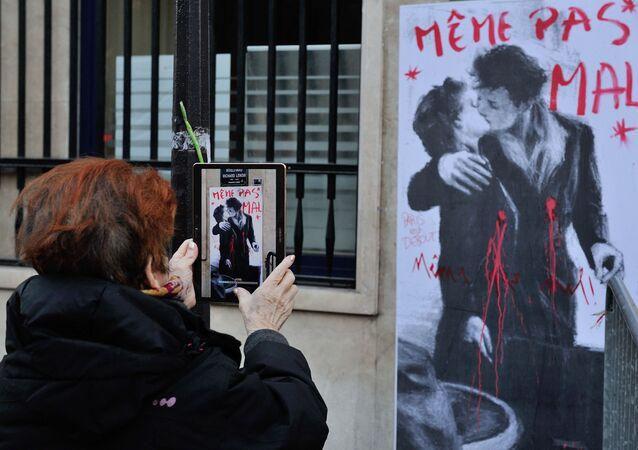 Kobieta robi zdjęcie graffiti w Paryżu