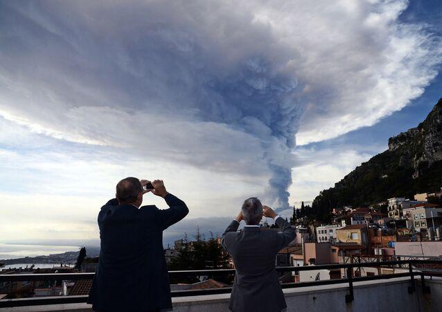 Ludzie patrzą na erupcję wulkanu Etna na Sycylii