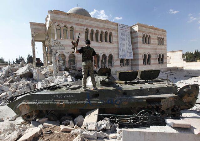 Bojownik Wolnej Armii Syrii na czołgu w pobliżu zniszczonego meczetu w mieście Azaz