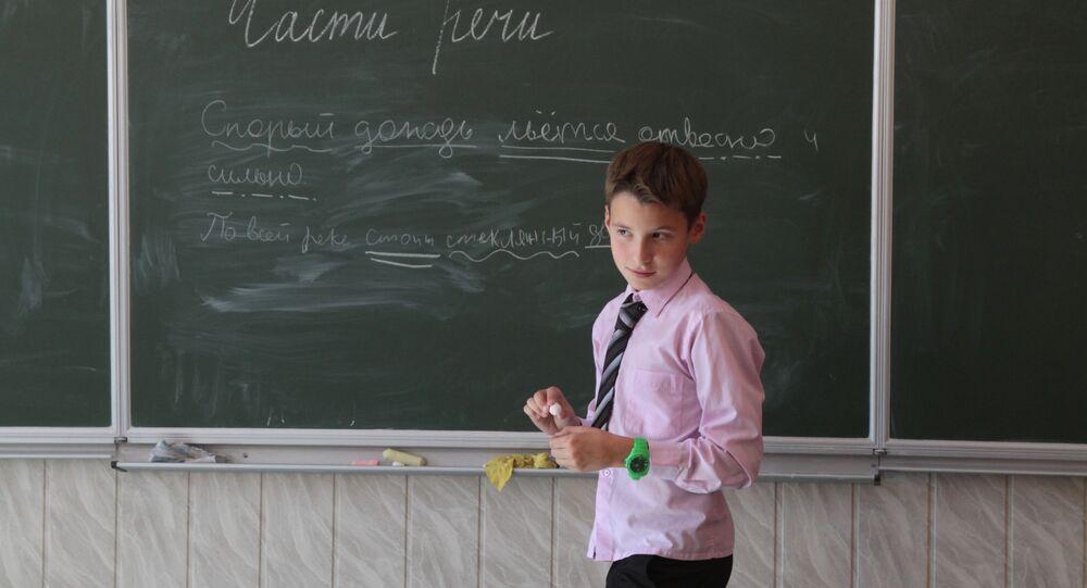 Uczeń u tablicy na lekcji języka rosyjskiego w gimnazjum w Kijowie