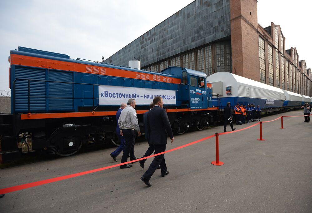 """Wicepremier Rosji Dmitrij Rogozin (drugi od lewej) ogląda specjalny skład przygotowany do wysyłki na powstający kosmodrom Wostocznyj rakiety nośnej """"Sojuz-2.1a"""" wykonany w Państwowym Rakietowo-Kosmicznym Centrum """"Progress""""."""