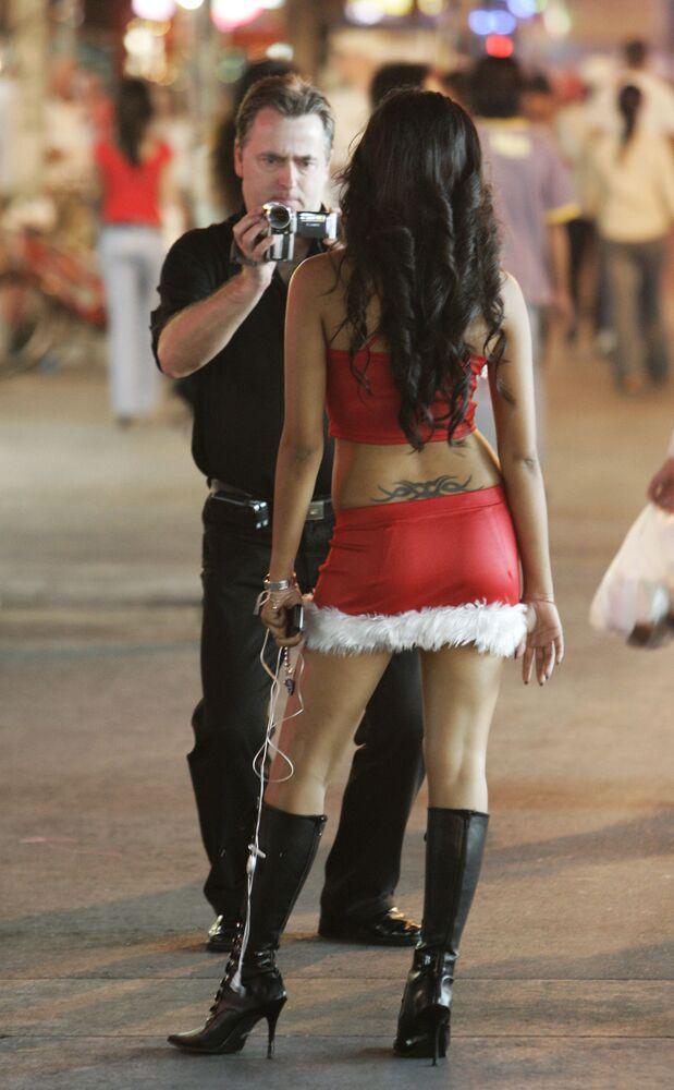 Tajska kobieta w zaimprowizowanym stroju świętego Mikołaja na plaży w Tajlandii