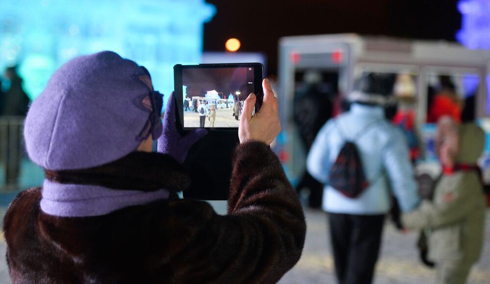 Kobieta robi zdjęcie na otwarciu festiwalu Lodowa Moskwa. W gronie rodziny