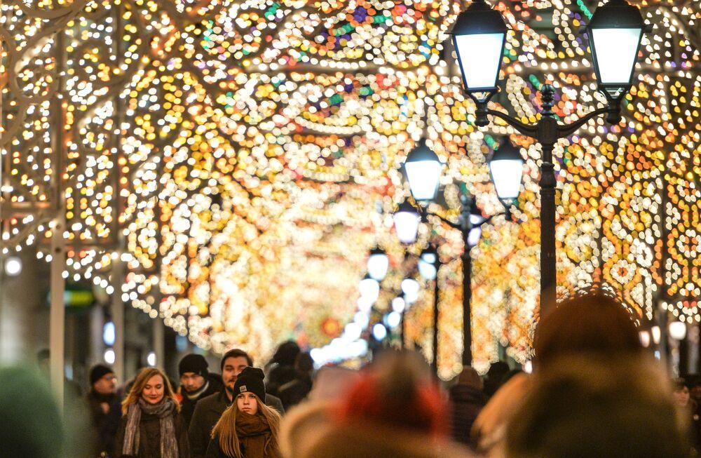 """Przechodnie na ulicy Nikolskiej w Moskwie, gdzie umieszczono instalacje świetlne w ramach Międzynarodowego Festiwalu """"Światło Bożego Narodzenia""""."""