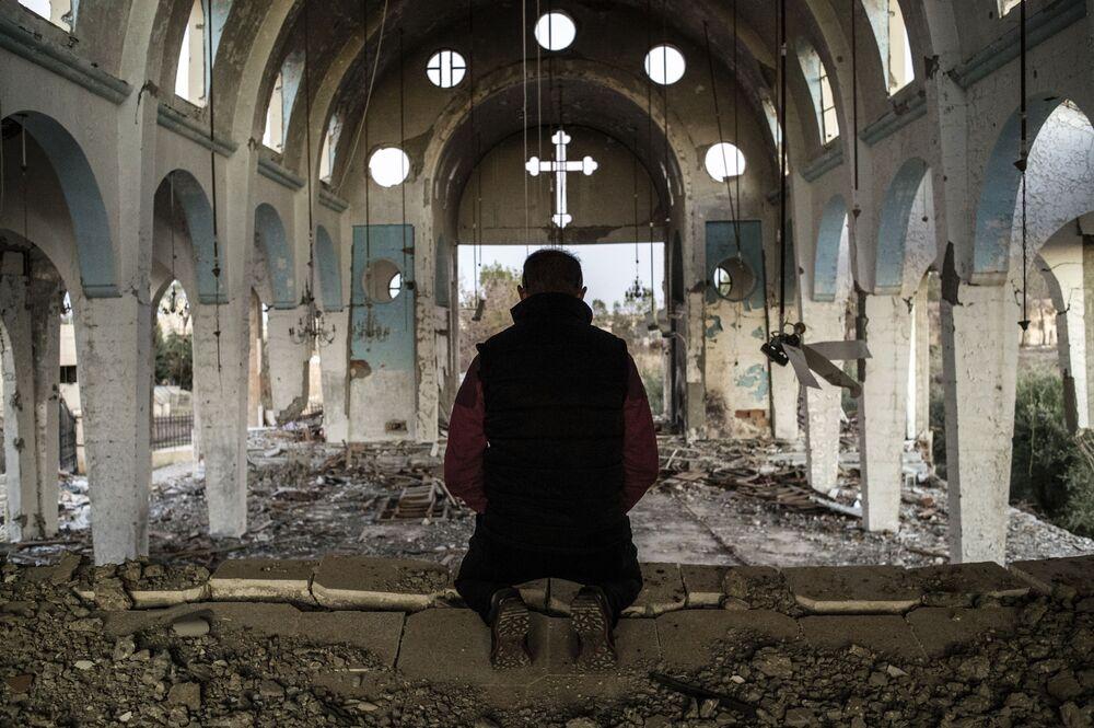 Mieszkaniec jednej z wiosek w prowincji El-Hasake na północnym wschodzie Syrii modli się w świątynii św. Jerzego znisczonej przez bojowników ISIS (Daesh).