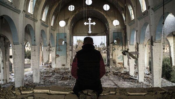 Mieszkaniec jednej z wiosek w prowincji El-Hasake na północnym wschodzie Syrii modli się w świątynii św. Jerzego znisczonej przez bojowników ISIS (Daesh). - Sputnik Polska
