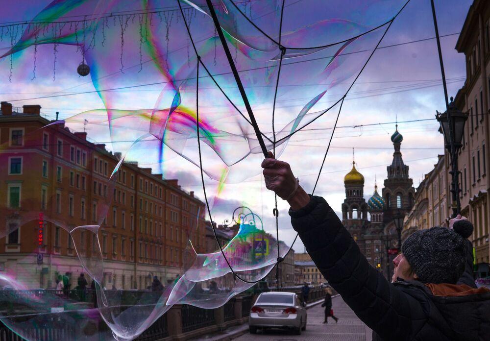 Uliczny artysta dmucha bański mydlane na wybrzeżu kanału Gribojedowa w Petersburgu.
