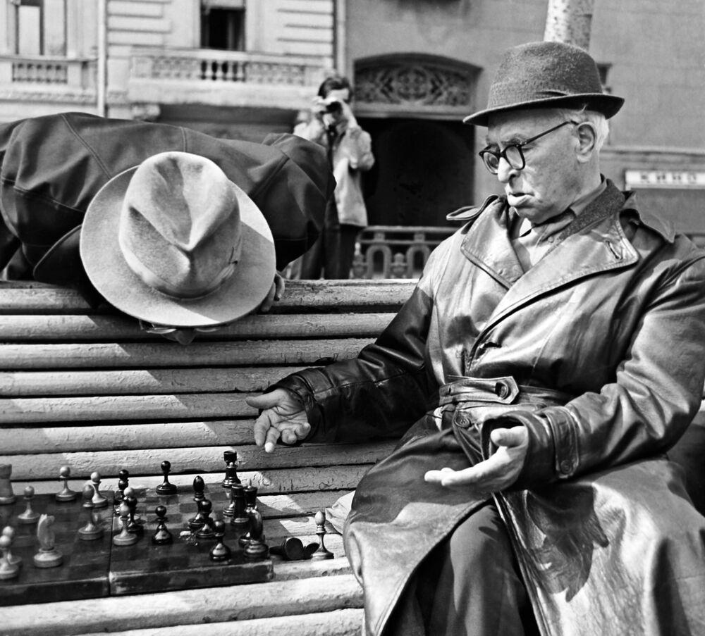 Emeryci grają w szachy na ławce w parku