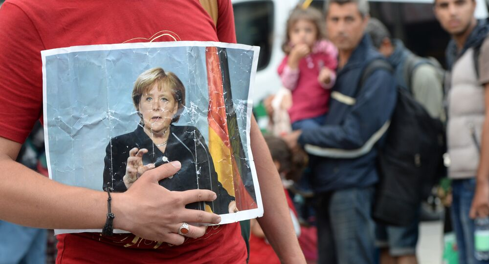A refugee holds a picture of German Chancellor Angela Merkel after the arrival of refugees at the main train station in Munich, southern Germany, September 05, 2015