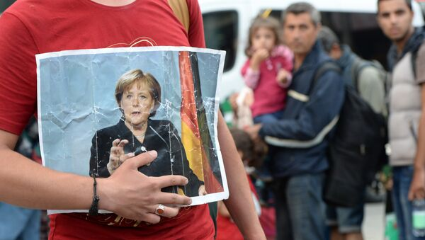 A refugee holds a picture of German Chancellor Angela Merkel after the arrival of refugees at the main train station in Munich, southern Germany, September 05, 2015 - Sputnik Polska