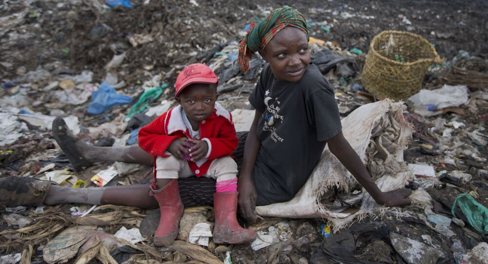 Kobieta z dzieckiem zbierają śmieci na wysypisku w Nairobi w Kenii
