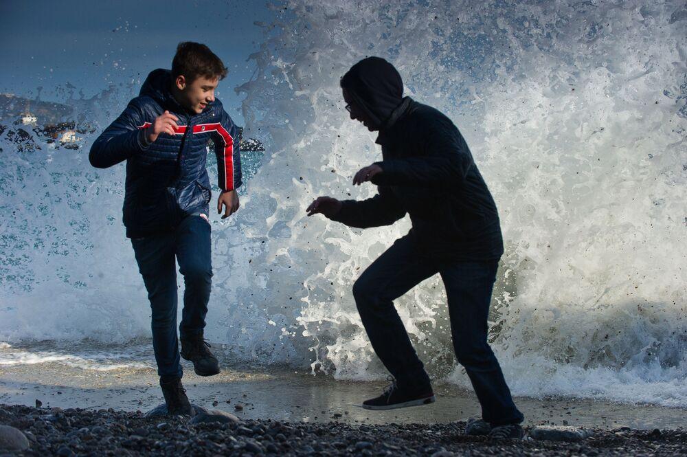 Dzieci uciekają od morskiej fali na wybrzeżu Jałty