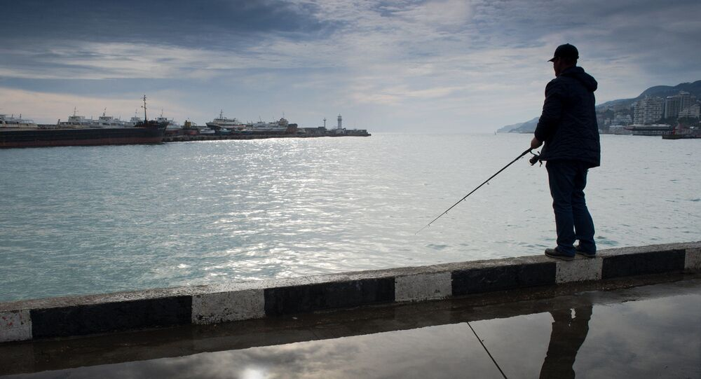Mężczyzna łowi rybę na Krymie