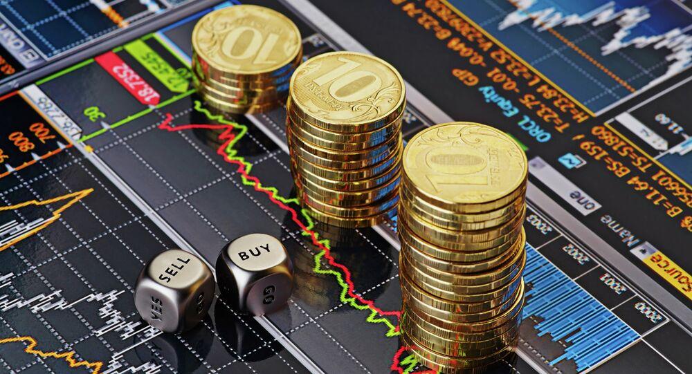 Monety 10-rublowe na ekranie z wykresami giełdowymi