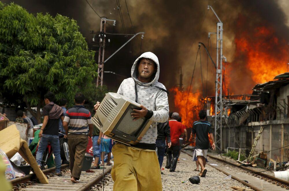 Mężczyzna ratuje telewizor z ognia w Indonezji