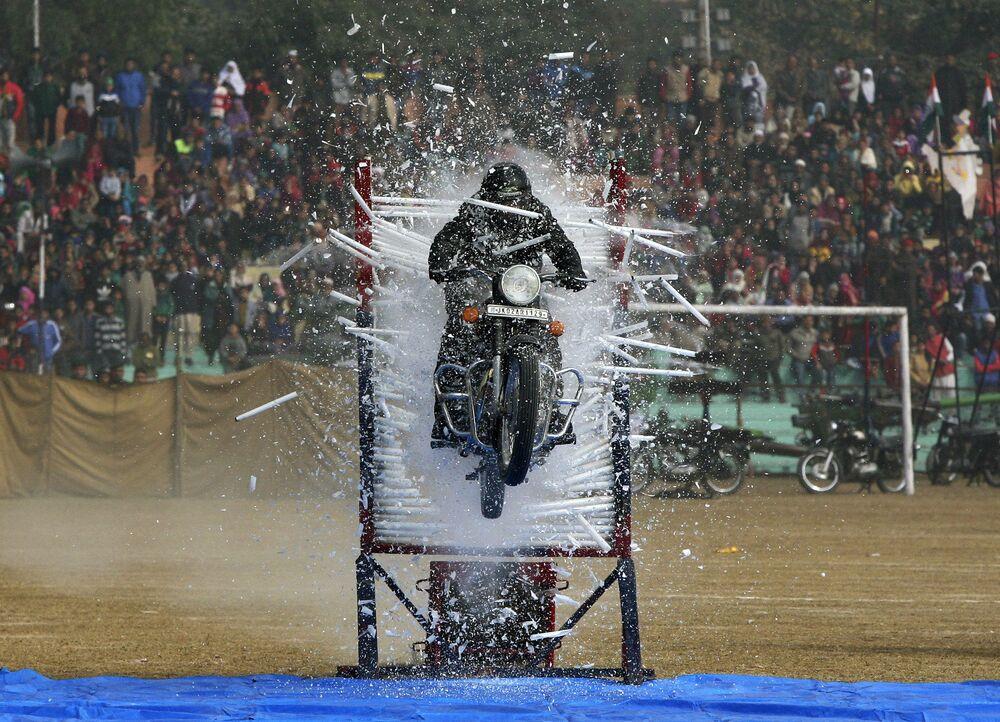 Indyjski policjant wykonuje wyczyn akrobatyczny na motocyklu podczas parady z okazji Dnia Republiki w Jammu, Indie