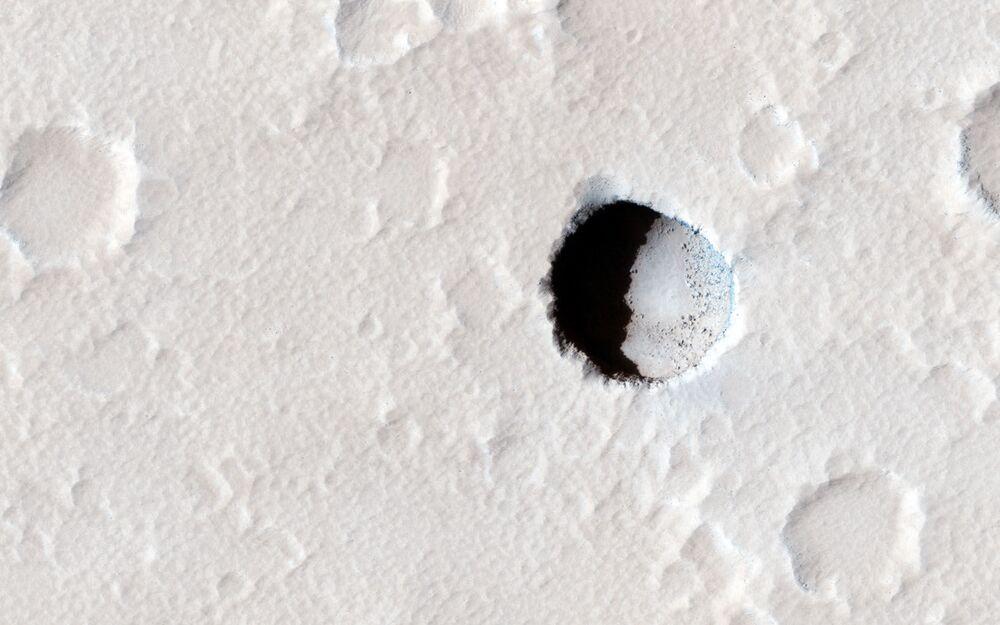 Głęboki krater na południowo-wschodnim stoku marsjańskiej góry Elysium Mons
