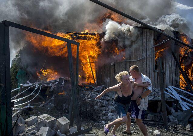 Mieszkańcy uciekają od pożaru w domu zniszczonym przez atak Sił Zbrojnych Ukrainy na wsi Ługanskaja