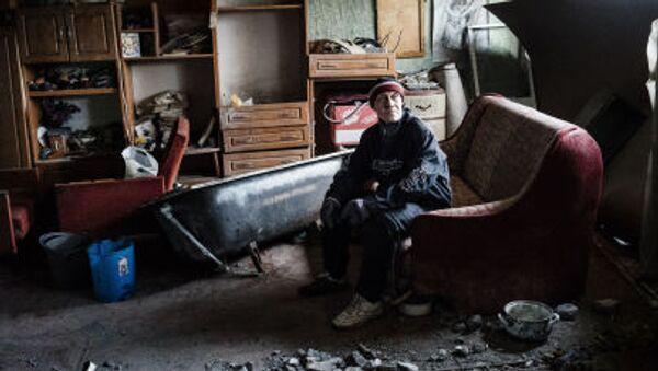 Mężczyzna w zniszczonym mieszkaniu w Doniecku - Sputnik Polska