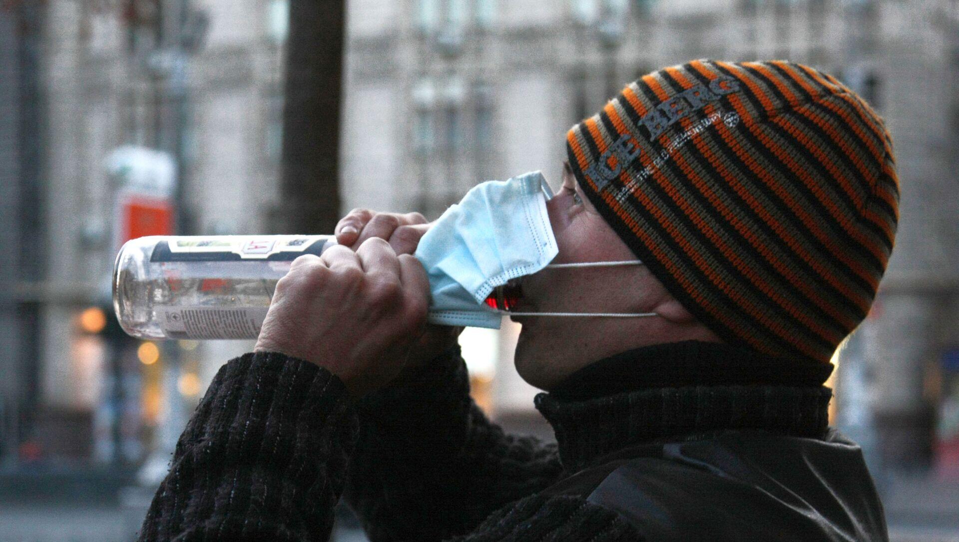 Mieszkaniec Kijowa w masce ochronnej pije wódkę - Sputnik Polska, 1920, 18.04.2021