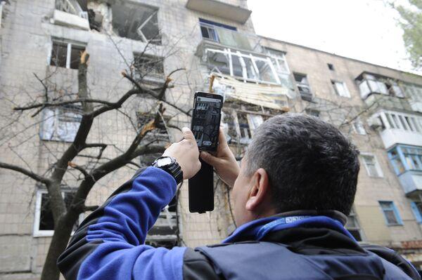 Pracownik misji OBWE ogląda dom, uszkodzony w wyniku ostrzału Doniecka - Sputnik Polska