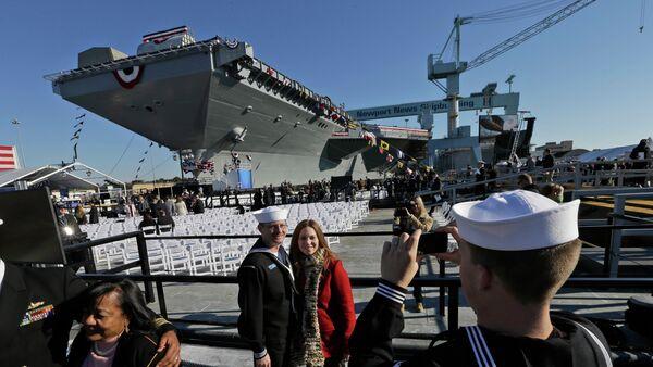 Pozujący na tle USS Gerald R. Ford - Sputnik Polska