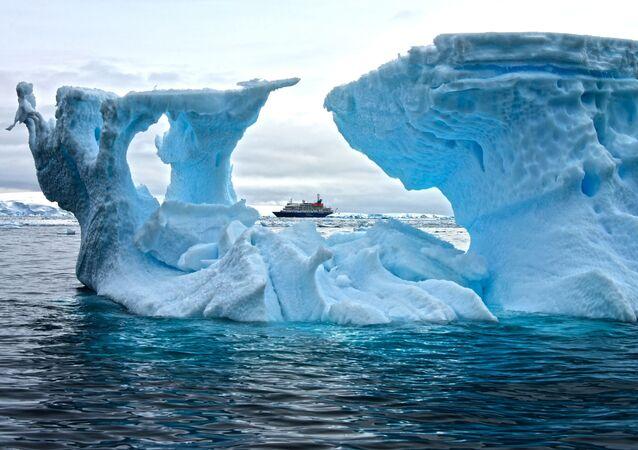 Statek na tle góry lodowej na Antarktydzie