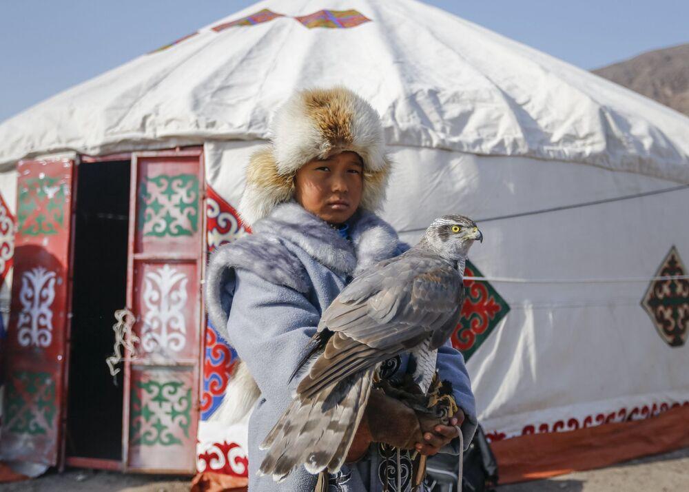 Młody myśliwy z sokołem podczas tradycyjnych zawodów myśliwskich w miejscowości Nura w Kazachstanie