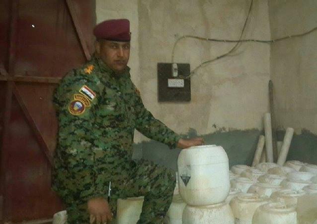 Iracki żołnnierz pokazuje broń chemiczną wykorzystywaną przez Daesh. Prowincja Anbar, Irak