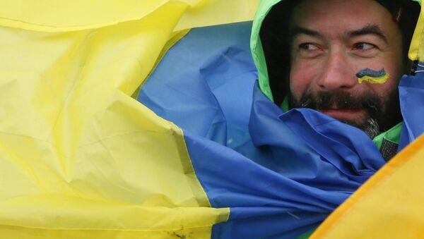 Mężczyzna owinięty we flagę Ukrainy - Sputnik Polska